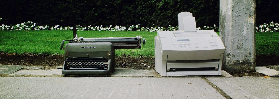 A typewriter and an old printer on a street next to a park