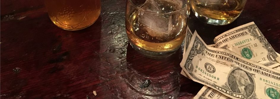 Smaller picture of Dollar notes and whisky on a wooden table