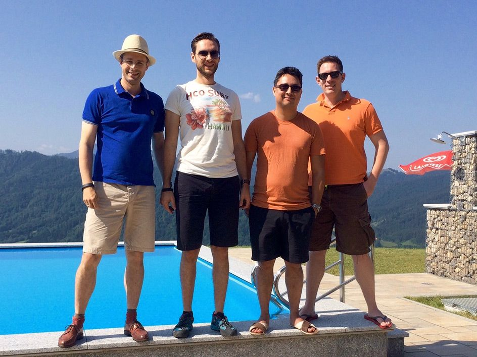 4 men standing on a swimming pool