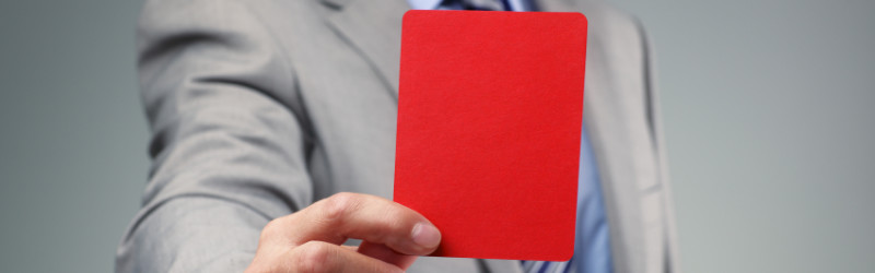Man with tie and suit holding a red card