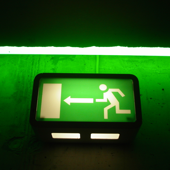 smaller picture of green emergency exit sign on a green background